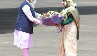 In this photo provided by Prime Minister of India Narendra Modi's twitter handle, Indian Prime Minister Narendra Modi receives a bouquet of flowers from Bangladesh's Prime Minister Sheikh Hasina in Dhaka, Bangladesh, Friday, March 26, 2021. Modi arrived in Bangladesh's capital on Friday to join celebrations marking 50 years of the country's independence, but his trip was not welcomed by all. The two-day visit, his first foreign trip since the coronavirus pandemic began last year, will also include joining commemorations for 100 years since the birth of independence leader Sheikh Mujibur Rahman, the father of current Prime Minister Sheikh Hasina. (Prime Minister of India Narendra Modi's twitter handle via AP Photo)