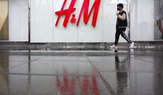 A man carrying an umbrellas walks past an H&M clothing store at a shopping mall in Beijing, Friday, March 26, 2021. H&M disappeared from the internet in China as the government raised pressure on shoe and clothing brands and announced sanctions Friday against British officials in a spiraling fight over complaints of abuses in the Xinjiang region. (AP Photo/Mark Schiefelbein)