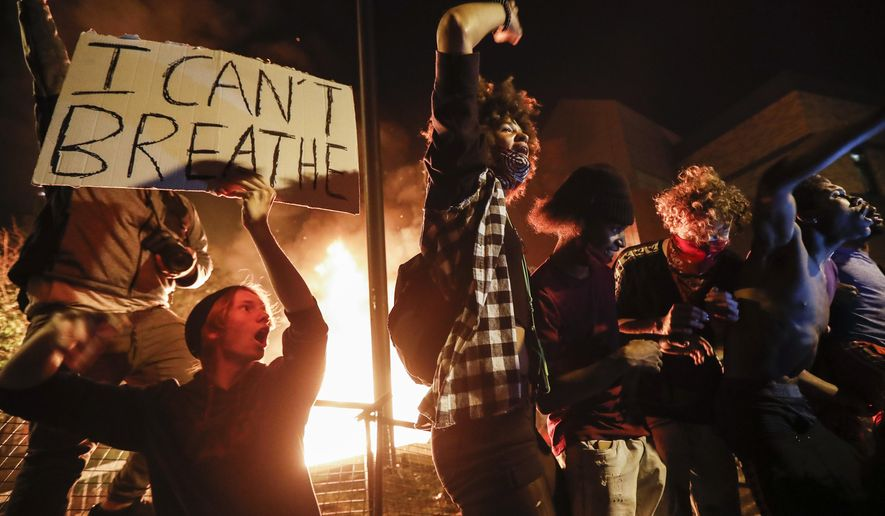 In this May 28, 2020, protesters demonstrate outside of a burning Minneapolis 3rd Police Precinct in Minneapolis. (AP Photo/John Minchillo, File)  **FILE**