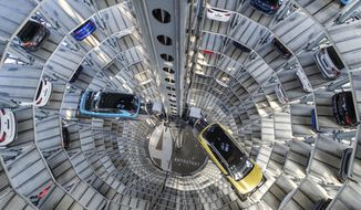 A Volkswagen ID.3 (l) and ID.4 stand inside a delivery tower in Wolfsburg, Germany, Friday, March 26, 2021. Volkswagen started deliveries of the all-electric SUV on 26 March 2021. (Ole Spata/dpa via AP)