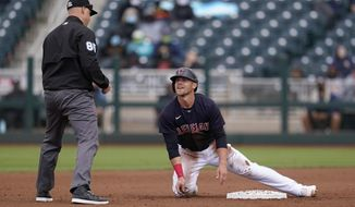 Cleveland Indians' Jake Bauers talks with umpire Nic Lentz, left, after being called out trying to steal second base during the fourth inning of a spring training baseball game against the San Francisco Giants Tuesday, March 23, 2021, in Goodyear, Ariz. (AP Photo/Ross D. Franklin)