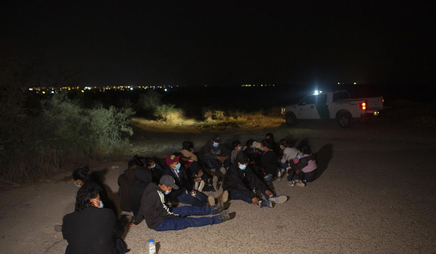 Migrants, mostly from Guatemala, wait at a U.S. Border Patrol intake site after they were smuggled on an inflatable raft across the Rio Grande river in Roma, Texas, Wednesday, March 24, 2021. On Wednesday, President Joe Biden tapped Vice President Kamala Harris to lead the White House efforts at the U.S. southern border and work with Central American nations to address root causes of the migration. The lights of the Mexican city of Miguel Aleman can be seen in the background. (AP Photo/Dario Lopez-Mills) ** FILE **