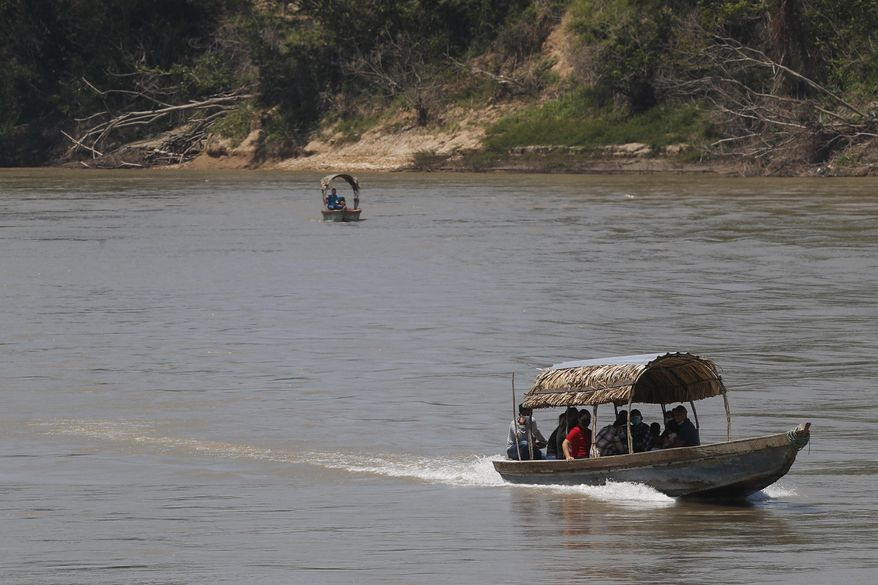 Migrants cross the Usumacinta River on boats from Guatemala, to Frontera Corozal, Chiapas state, Mexico, Wednesday, March 24, 2021. Mexico wants again to appear cooperative like it was in 2019 when under threat of tariffs from then-President Donald Trump it deployed soldiers to slow down the flow of migrants from Central America, but the reality here is business as usual as entire communities live off migrants headed north for reasons now familiar: violence, an inability to support their families, the devastation wrought by two major hurricanes that hit Central America in November and egged on by rampant misinformation. (AP Photo/Eduardo Verdugo)