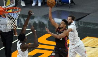 Portland Trail Blazers guard CJ McCollum, center, shoots as he gets between Orlando Magic center Mo Bamba, left, and guard Michael Carter-Williams, right, during the second half of an NBA basketball game, Friday, March 26, 2021, in Orlando, Fla. (AP Photo/John Raoux)