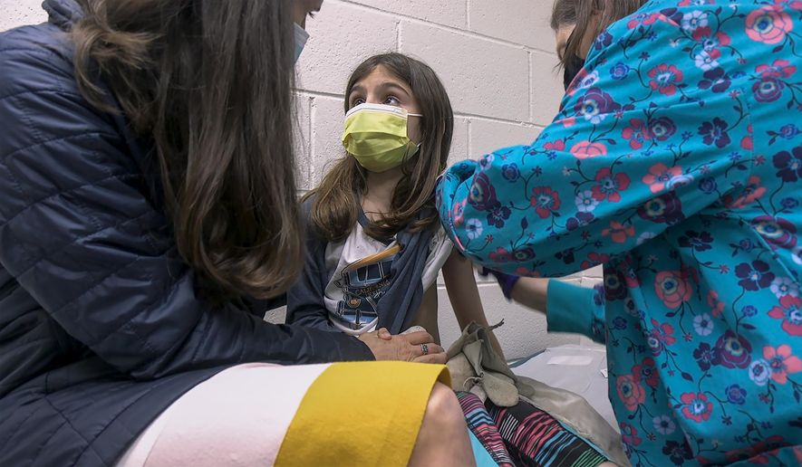 In this Wednesday, March 24, 2021, image from video provided by Duke Health, Alejandra Gerardo, 9, looks up to her mom, Dr. Susanna Naggie, as she gets the first of two Pfizer COVID-19 vaccinations during a clinical trial for children at Duke Health in Durham, N.C. In the U.S. and abroad, researchers are beginning to test younger and younger kids, to make sure the shots are safe and work for each age. (Shawn Rocco/Duke Health via AP)