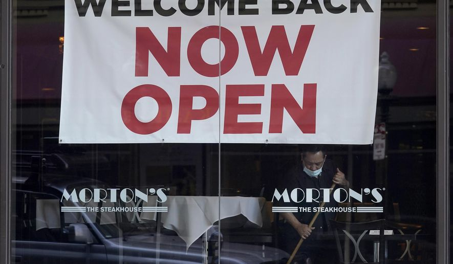 "In this March 4, 2021, file photo, a sign reading ""Welcome Back Now Open"" is posted on the window of a Morton's Steakhouse restaurant as a man works inside during the coronavirus pandemic in San Francisco. California added 141,000 jobs in February as more than a quarter of a million people returned to the workforce. The California Employment Development Department said Friday, March 26, that the state's unemployment rate in February was 8.5%, down from 9% in January. (AP Photo/Jeff Chiu, File)"
