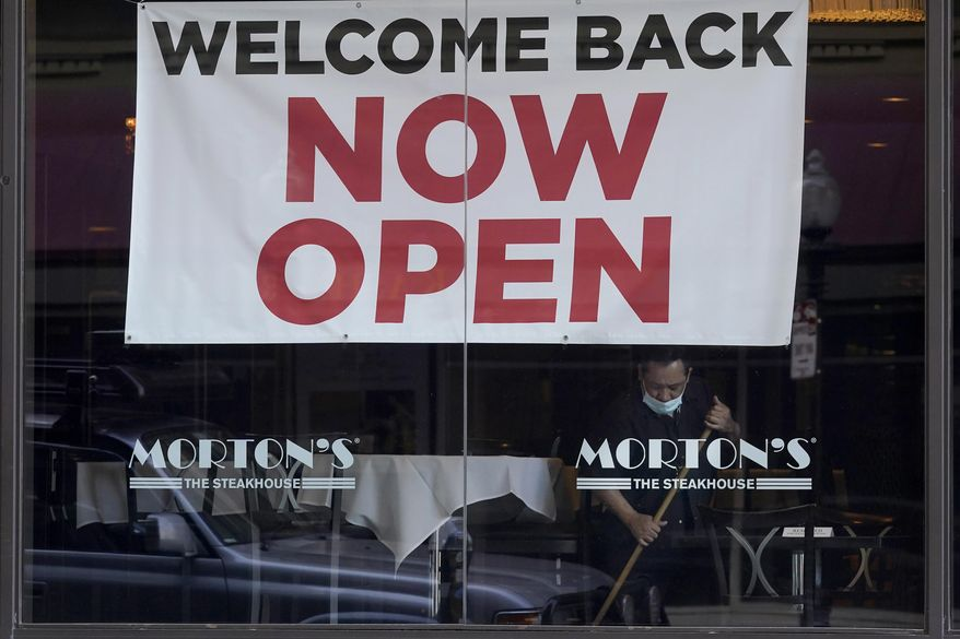 """In this March 4, 2021, file photo, a sign reading """"Welcome Back Now Open"""" is posted on the window of a Morton's Steakhouse restaurant as a man works inside during the coronavirus pandemic in San Francisco. California added 141,000 jobs in February as more than a quarter of a million people returned to the workforce. The California Employment Development Department said Friday, March 26, that the state's unemployment rate in February was 8.5%, down from 9% in January. (AP Photo/Jeff Chiu, File)"""