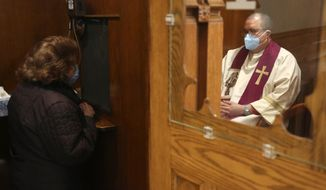 The Rev. Manuel Rodriguez listens to a parishioner's confession at Our Lady of Sorrows in the Queens borough of New York on Saturday, March 20, 2021. The Roman Catholic church reopened for in-person services in July 2020 and recently resumed in-person confessions. (AP Photo/Jessie Wardarski)