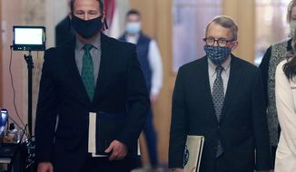 FILE— In this April 15, 2020, file photo, Ohio Lt. Gov. Jon Husted, left, and Gov. Mike DeWine, walk into their daily coronavirus news conference at the Ohio Statehouse in Columbus, Ohio. Records show that DeWine unsuccessfully proposed a compromise to legislation restricting the state's ability to respond to a public health order emergency. In proposals made last weekend by Husted to House Speaker Bob Cupp and Senate President Matt Huffman, DeWine signaled he would support the bill if it called for governors' emergency declarations and orders to remain in place as they do now unless the Legislature acts. (Doral Chenoweth/The Columbus Dispatch via AP, File)