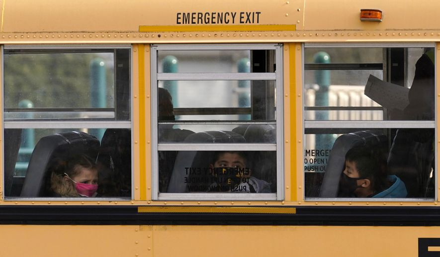 Elementary school students sit on board a school bus after attending in-person classes at school in Wheeling, Illinois, Nov. 19, 2020. (AP Photo/Nam Y. Huh) ** FILE **