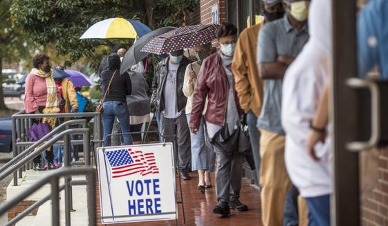 People wait in line on the first day of advance voting for Georgia's Senate runoff election at the Bell Auditorium in Augusta, Ga. (Michael Holahan/The Augusta Chronicle via AP, File)