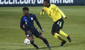 USA's Yunus Musah, left, duels for the ball with Jamaica's Chavany Willis during the international friendly soccer match between USA and Jamaica at SC Wiener Neustadt stadium in Wiener Neustadt, Austria, Thursday, March 25, 2021. (AP Photo/Ronald Zak)