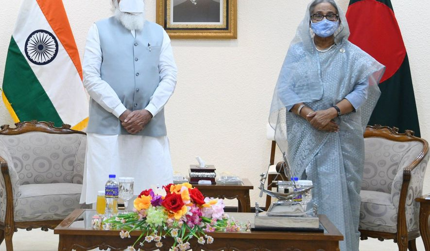 In this photo provided by Prime Minister of India Narendra Modi's twitter handle, Indian Prime Minister Narendra Modi and Bangladesh's Prime Minister Sheikh Hasina stands for a photograph in Dhaka, Bangladesh, Friday, March 26, 2021. Modi on Saturday concluded his two-day official visit to Bangladesh amid both violent protests and enthusiasm that the bilateral relations between the two neighbors would continue to grow. (Prime Minister of India Narendra Modi's twitter handle via AP Photo)
