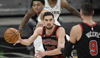 Chicago Bulls' Tomas Satoransky (31) passes the ball to teammate Nikola Vucevic (9) as San Antonio Spurs' Keldon Johnson looks on during the second half of an NBA basketball game on Saturday, March 27, 2021, in San Antonio. (AP Photo/Darren Abate)