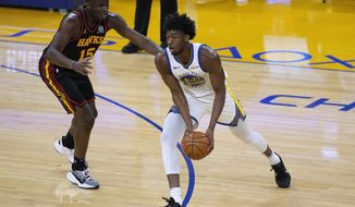 Golden State Warriors center James Wiseman (33) moves the ball past Atlanta Hawks center Clint Capela (15) during the first half of an NBA basketball game in San Francisco, Friday, March 26, 2021. (AP Photo/Tony Avelar)
