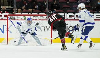 Tampa Bay Lightning goaltender Andrei Vasilevskiy, of Russia, defends while Carolina Hurricanes left wing Jordan Martinook (48) shoots against Lightning defenseman Andreas Borgman (5), of Sweden, during the first period of an NHL hockey game in Raleigh, N.C., Saturday, March 27, 2021. (AP Photo/Gerry Broome)