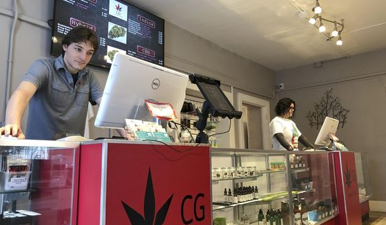 FILE - In this March 6, 2019, file photo, Korbin Osborn, left, works as a cannabis adviser at a medical marijuana dispensary in Santa Fe, N.M. Legislation to legalize cannabis in New Mexico advanced Thursday, March 18, 2021, toward a decisive Senate floor vote under a framework that emphasizes government oversight of pricing and supplies and social services for communities where the criminalization of pot led to aggressive policing.  (AP Photo/Morgan Lee, File)