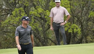 Bubba Watson, right, looks over the No. 17 green after hitting his tee shot into a hazard during a round of 16 match at the Dell Technologies Match Play Championship golf tournament Saturday, March 27, 2021, in Austin, Texas. At left is Brian Harman, who won the hole and the match. (AP Photo/David J. Phillip)