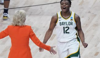 Baylor guard Moon Ursin (12) and head coach Kim Mulkey celebrate the team's overtime win over Michigan in a college basketball game in the Sweet Sixteen round of the women's NCAA tournament at the Alamodome in San Antonio, Saturday, March 27, 2021. (AP Photo/Eric Gay)