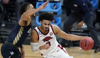 Arkansas forward Justin Smith (0) drives around Oral Roberts forward Kevin Obanor, left, during the first half of a Sweet 16 game in the NCAA men's college basketball tournament at Bankers Life Fieldhouse, Saturday, March 27, 2021, in Indianapolis. (AP Photo/Jeff Roberson)