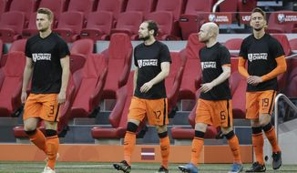 Netherlands' players enters on the field with shirt reading ' football support change' prior to the start of the World Cup 2022 group G qualifying soccer match between The Netherlands and Latvia at the Johan Cruyff ArenA in Amsterdam, Netherlands, Saturday, March 27, 2021. (AP Photo/Peter Dejong)