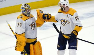 Nashville Predators goaltender Juuse Saros, left, celebrates with defenseman Mattias Ekholm after the Predators defeated the Chicago Blackhawks in an NHL hockey game in Chicago, Saturday, March 27, 2021. (AP Photo/Nam Y. Huh)