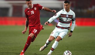 Serbia's Sergej Milinkovic-Savic, left, and Portugal's Cristiano Ronaldo challenge for the ball during the World Cup 2022 group A qualifying soccer match between Serbia and Portugal at the Rajko Mitic stadium in Belgrade, Serbia, Saturday, March 27, 2021. (AP Photo/Darko Vojinovic)