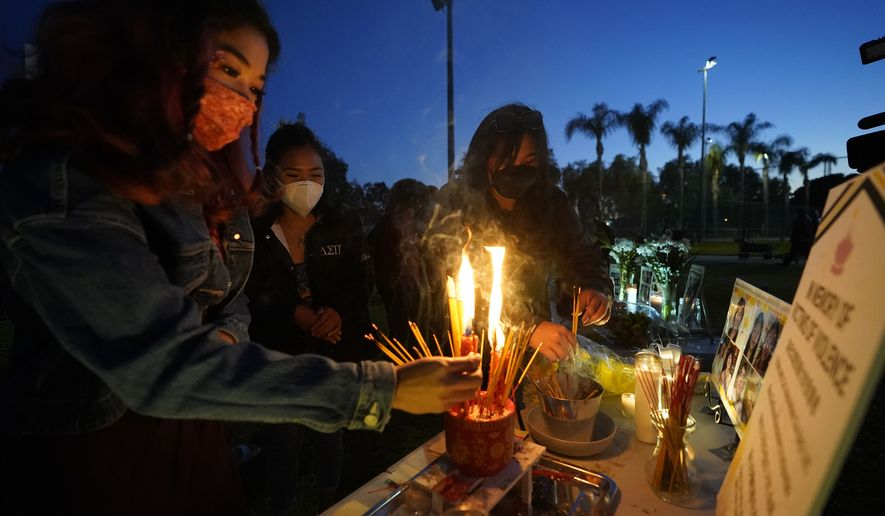 Women pay theirs respects at a memorial in honor of the victims of the shootings in Atlanta, where eight people were killed the week before, during a candle vigil in Monterrey Park, Calif., late Saturday, March 27, 2021. The shootings at three Georgia massage parlors and spas that left eight people dead, six of them women of Asian descent, come on the heels of a recent wave of attacks against Asian Americans since the coronavirus entered the United States. (AP Photo/Damian Dovarganes)