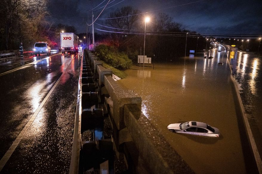 A car is seen submerged on I-24 under Antioch Pike in Nashville, Tenn., Sunday, March 28, 2021. Heavy rain across Tennessee flooded homes and roads early Sunday, prompting officials to rescue numerous people from houses, apartments and vehicles as a line of severe storms crossed the state. (Andrew Nelles/The Tennessean via AP)