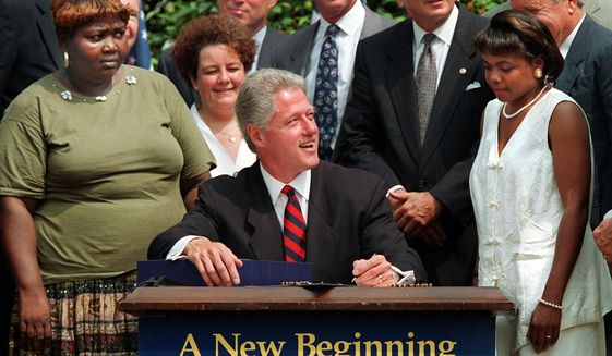 In this Aug. 22, 1996, file photo President Bill Clinton prepares to sign legislation in the Rose Garden of the White House overhauling America's welfare system. Visible, from left, are former welfare recipients Lillie Harden, of Little Rock, Ark., and Janet Ferrel, of W.Va., Vice President Gore, West Virginia Gov. Gaston Caperton, Sen. John Breaux, D-La., and former welfare recipient Penelope Howard, of Delaware. (AP Photo/J. Scott Applewhite, File)  **FILE**