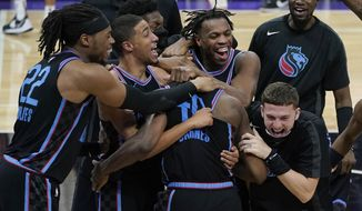 Sacramento Kings forward Harrison Barnes, foreground middle, is congratulated by teammates after shooting the game-winning 3-point basket in the team's NBA basketball game against the Cleveland Cavaliers in Sacramento, Calif., Saturday, March 27, 2021. (AP Photo/Jeff Chiu)