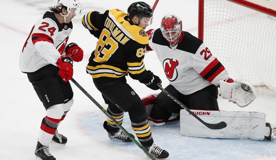 Boston Bruins' Karson Kuhlman (83) cannot get a shot off against New Jersey Devils' Ty Smith (24) and Mackenzie Blackwood (29) during the first period of an NHL hockey game, Sunday, March 28, 2021, in Boston. (AP Photo/Michael Dwyer)