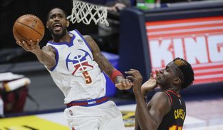 Denver Nuggets forward Will Barton (5) lays up the ball against Atlanta Hawks center Clint Capela (15) during the first quarter of an NBA basketball game in Denver, Sunday, March 28, 2021. (AP Photo/Joe Mahoney)