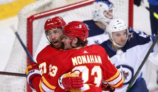 Calgary Flames' Josh Leivo (27) celebrates his goal with Sean Monahan in front of Winnipeg Jets goalie Laurent Brossoit and Jets' Neal Pionk during the first period of an NHL hockey game Saturday, March 27, 2021, in Calgary Alberta. (Todd Kool/The Canadian Press via AP)