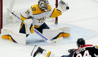 Nashville Predators goaltender Pekka Rinne, top, makes a save on a shot by Chicago Blackhawks center Pius Suter during the third period of an NHL hockey game in Chicago, Sunday, March 28, 2021. (AP Photo/Nam Y. Huh)