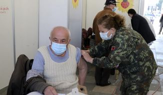 A man receives a dose of Sinovac COVID-19 vaccine in Tirana, Albania, Sunday, March 28, 2021. Albania started a mass vaccination campaign trying to inoculate half a million people opening the way to a more relaxed incoming summer tourism season. (AP Photo/Hektor Pustina)