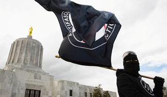 An antifascist protester flies a flag in front of the Oregon State Capitol building during an anti-fascist rally in Salem, Oregon, U.S., March 28, 2021. (REUTERS/Maranie R. Staab)