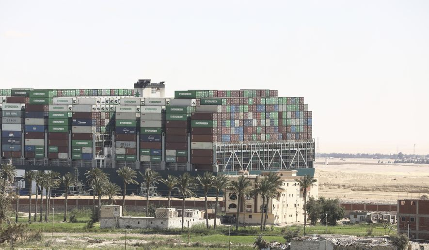 "Ever Given, a Panama-flagged cargo ship blocks the Suez Canal almost a week after it got stuck sideways in the crucial waterway, Monday, March 29, 2021. Engineers on Monday ""partially refloated"" the colossal container ship that continues to block traffic through the Suez Canal, a canal services firm said, without providing further details about when the vessel would be fully set free. (AP Photo/Mohamed Elshahed)"