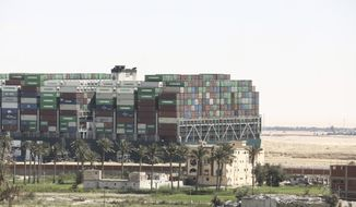"""Ever Given, a Panama-flagged cargo ship blocks the Suez Canal almost a week after it got stuck sideways in the crucial waterway, Monday, March 29, 2021. Engineers on Monday """"partially refloated"""" the colossal container ship that continues to block traffic through the Suez Canal, a canal services firm said, without providing further details about when the vessel would be fully set free. (AP Photo/Mohamed Elshahed)"""