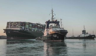 """In this photo released by Suez Canal Authority, the Ever Given, a Panama-flagged cargo ship is pulled by one of the Suez Canal tugboats, in the Suez Canal, Egypt, Monday, March 29, 2021. Engineers on Monday """"partially refloated """" the colossal container ship that continues to block traffic through the Suez Canal, authorities said, without providing further details about when the vessel would be set free. (Suez Canal Authority via AP)"""