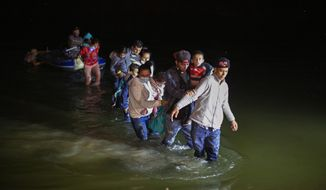 Migrant families, mostly from Central American countries, wade through shallow waters after being delivered by smugglers on small inflatable rafts on U.S. soil in Roma, Texas, Wednesday, March 24, 2021. As soon as the sun sets, at least 100 migrants crossed through the Rio Grande river by smugglers into the United States. (AP Photo/Dario Lopez-Mills)