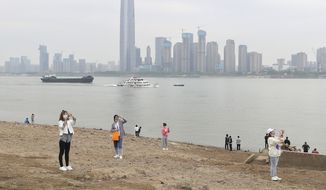 "Residents visit the Yangtze River in Wuhan in central China's Hubei province Monday, March 29, 2021. A joint WHO-China study on the origins of COVID-19 says that transmission of the virus from bats to humans through another animal is the most likely scenario and that a lab leak is ""extremely unlikely,"" according to a draft copy obtained by The Associated Press. (Chinatopix Via AP)"