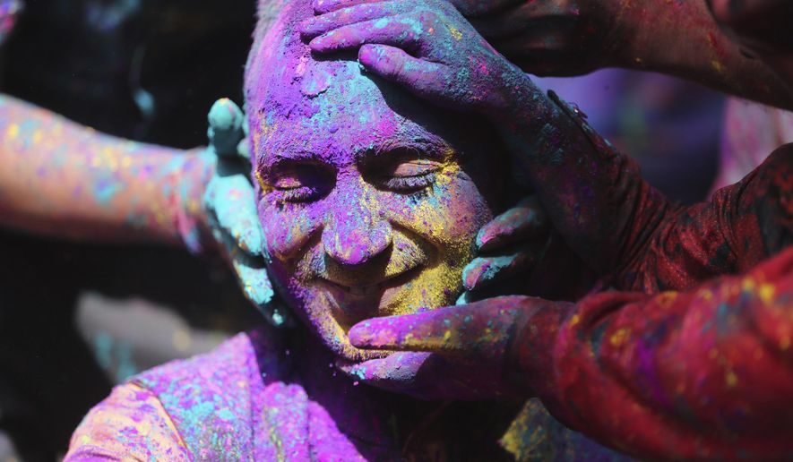 Indians smear colored powder on each other as they celebrate Holi in Jammu, India, Sunday, March 28, 2021. Holi, the Hindu festival of colors, also heralds the arrival of spring. (AP Photo/Channi Anand)