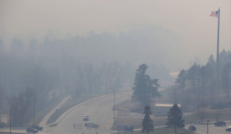 Smoke from a wildfire in the Black Hills of South Dakota blankets an area on the outskirts of Rapid City, S.D., where police set up a roadblock on Monday, March 29, 2021. There were at least three wildfires west that were burning west of Rapid City on a day when wind gusts ranged from 50 to 72 mph. The Pennington County Sheriff's Office said at least 400 homes had been evacuated and about 250 firefighters were battling the blaze that started near the town of Nemo. (Siandhara Bonnet/Rapid City Journal via AP)