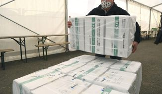 An employee unloads the newly arrived coronavirus vaccines from Chinese pharmaceutical company Sinopharm at the logistics base set up to in the parking lot of the government office in the 13th district of Budapest, Hungary, Monday, March 29, 2021. (Noemi Bruzak/MTI via AP)