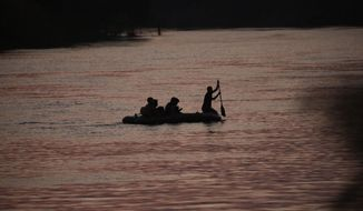 A smuggler paddles a small inflatable raft across the Rio Grande from Mexico into the U.S. carrying migrant families in Roma, Texas, Wednesday, March 24, 2021. (AP Photo/Dario Lopez-Mills) ** FILE **