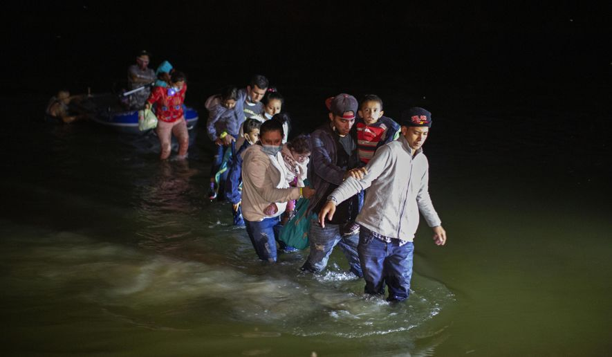 Migrant families, mostly from Central American countries, wade through shallow waters after being delivered by smugglers on small inflatable rafts on U.S. soil in Roma, Texas, Wednesday, March 24, 2021. As soon as the sun sets, at least 100 migrants crossed through the Rio Grande river by smugglers into the United States. (AP Photo/Dario Lopez-Mills) **FILE**
