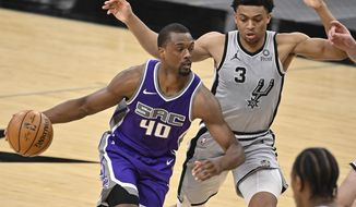 Sacramento Kings' Harrison Barnes (40) drives around San Antonio Spurs' Keldon Johnson during the second half of an NBA basketball game on Monday, March 29, 2021, in San Antonio. (AP Photo/Darren Abate)