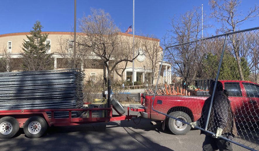 Workers remove segments of the chain-link fence around the New Mexico state capitol in Santa Fe on Saturday, March 27, 2021. The fence was erected by National Guardsman and State Police officers following Jan. 6, 2021, riots in Washington, D.C. The added security cost at least $700,000 with over $15,000 going for the fence rental, according to a March 12, 2021, response from state officials that did not include the cost of removing it. (AP Photo/Cedar Attanasio)