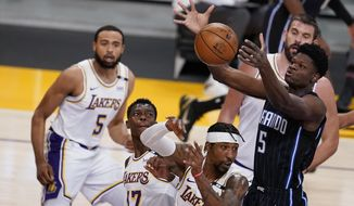 Orlando Magic center Mo Bamba (5) grabs a rebound over Los Angeles Lakers guard Kentavious Caldwell-Pope (1) and Dennis Schroder (17) during the first half of an NBA basketball game Sunday, March 28, 2021, in Los Angeles. (AP Photo/Marcio Jose Sanchez)